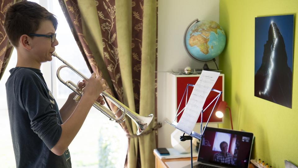 Ein Junge übt Trompete, sein Lehrer kommt aus dem Tablet auf der Kommode.