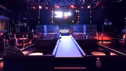 """Foto einer Videoprojektion in einem Night-Club. Unter der Leinwand steht """"Their night is our day"""". Im Raum sitzen Menschen in den Separee-artigen Sitzmöbeln. In der Mitte ist eine Art Laufsteg zu sehen."""