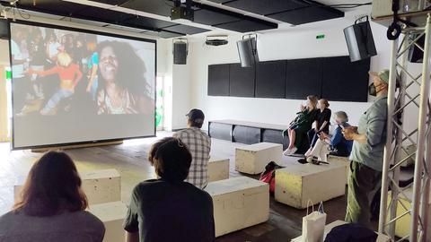In einem abgedunkelten Raum sitzen Menschen auf provisorisch aufgebauten Bänken und schauen auf eine temporäre Leinwand, die mitten im Raum steht und ein Musikvideo zeigt.
