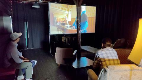 In einem abgedunkelten Raum sitzen Menschen auf Loungesesseln und schauen auf eine temporäre Leinwand, die mitten im kleinen Raum steht und ein Musikvideo zeigt.