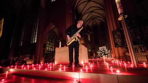 1.000 Kerzen erleuchten den Altarraum des Kaiserdoms St. Bartholomäus in Frankfurt zu den Saxophon-Klängen.