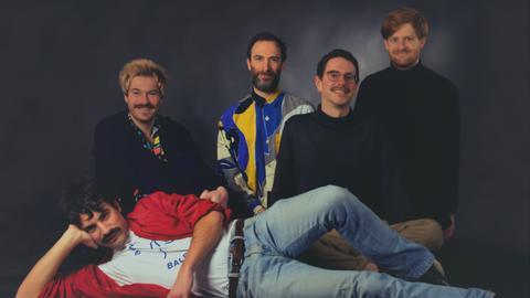 Fünf Männer im Stil eines 70er-Jahre-Fotostudios fotografiert