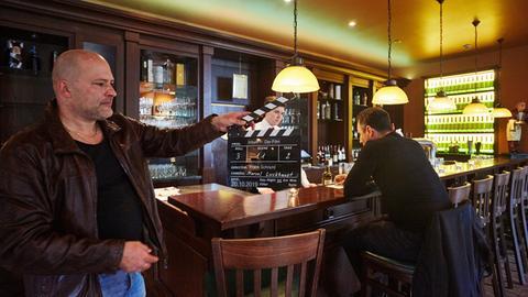 Frank Schraml schlägt die Regieklappe für eine Szene in einem Hotel zu.