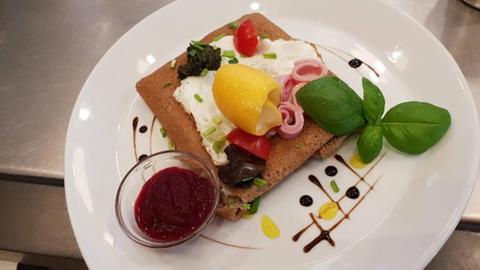 Ein Teller mit Brot, Aufstrich, Schinken, Zitrone, Tomate, Basilikumblatt und Saucenspiegel