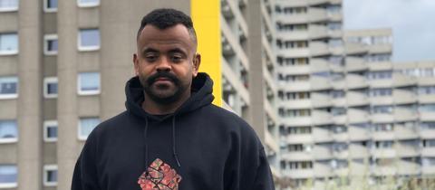Junger schwarzer Mann steht vor einem Hochhaus