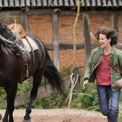 Mädchen rennt neben einem galoppierenden Pferd.