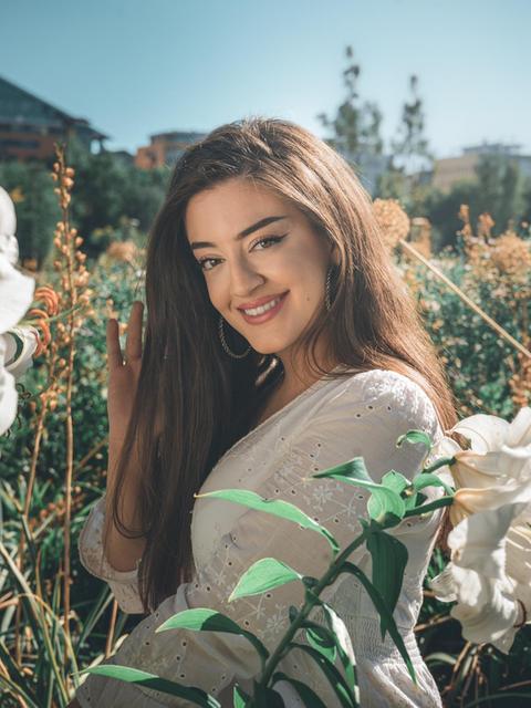 Parshad Esmaeili sitzt in einem Blumenfeld