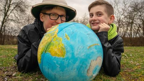 Zwei Kinder schauen einen Globus an.