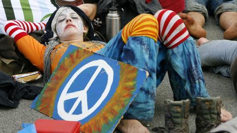 Eine Demonstrantin liegt schlummernd auf dem Boden - neben ihr steht ein gemaltes Peace-Zeichen auf einem Schild.