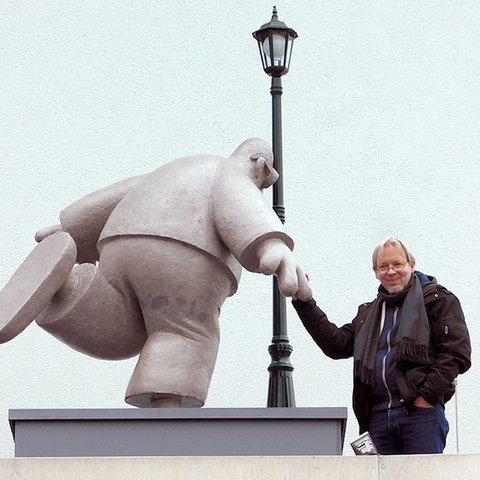 """Martin Perscheid steht neben dem """"Denkmal für den unbekannten Idioten"""" und reicht ihm die Hand."""
