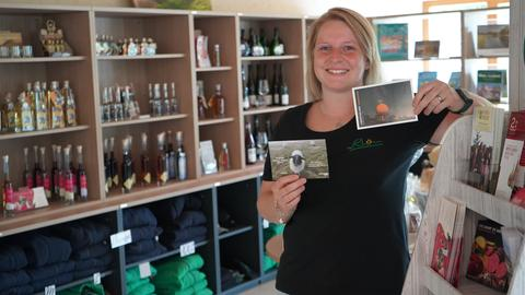 Junge Frau in einem Laden zeigt zwei Postkarten mit einem Schaf und einer Radar-Kuppel.