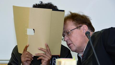 Der Angeklagte verbirgt sein Gesicht hinter einer Kladde und unterhält sich mit seinem Anwalt.