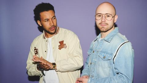 """Portrait des Duos """"Quarterhead"""" - Josh Tapen und Janik Riegert - vor einem lilafarbenen Hintergrund."""