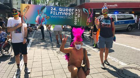Menschen tragen ein Banner vom Queer Filmfest Weiterstadt