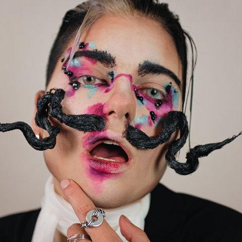 Das Bild zeigt eine Person, die direkt in die Kamera blickt. Der Mund ist geöffnet und pink verschmiert geschminkt. Die weißblond und schwarz gefärbten Haare sind zurückgegelt, die Augen lila und türkis geschminkt. Die Person trägt außerdem einen auffällig nach oben gezwirbelten schwarzen Schnurrbart.