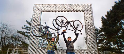 """Leon Groß und Vincent Keller mit ihren Rädern vor dem documenta 6-Kunstwerk """"Rahmenbau"""" oberhalb der Kasseler Karlsaue."""