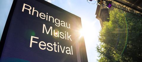 Infotafel mit Aufschrift Rheingau Musik Festival - darüber sind Bühnenscheinwerfer zu sehen