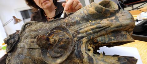 Eine Restauratorin arbeitet am Bronze-Pferdekopf.