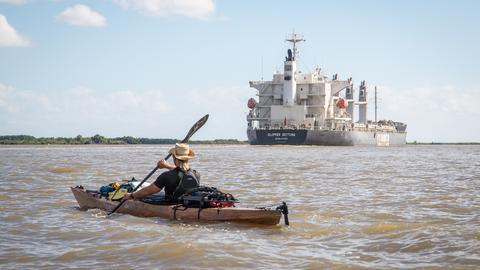 Mann im Kanu mit Tankschiff im Hintergrund