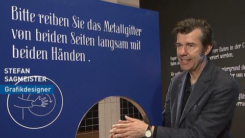 Stefan Sagmeister reibt in der Ausstellung an einem Metallgitter.