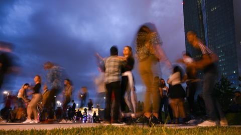 Tänzer in der Abend-Dämmerung, im Hintergrund das Hochhaus der EZB.