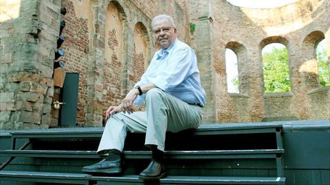 Laienschauspieler Hans-Jürgen Dietz sitzt auf der Bühne der Stiftsruine bei den Bad Hersfelder Festspielen.