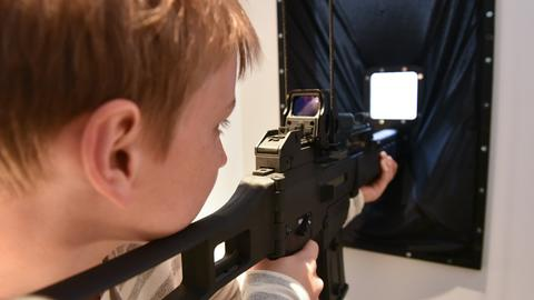 Ein Junge hält ein Plastik-Gewehr in der Hand und zielt durch ein Guckloch.