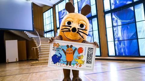 """Eine menschengroße Maus-Plüschfigur hält eine riesige """"Sendung mit der Maus""""-Briefmarke in den Pfoten."""