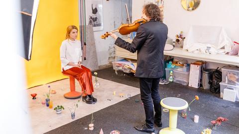Eine Besucherin, ein Musiker mit Geige, ausreichend Abstand dazwischen