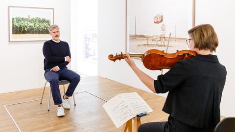 Eine Besucher, ein Musikerin, ausreichend Abstand dazwischen