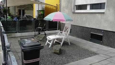 Schottergaten mit Bank und Sonnenschirm