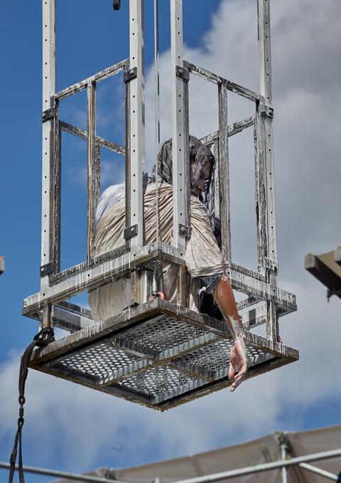 Ein mit weißer Farbe übergossener Schauspieler sitzt in einem Käfig, der in der Luft hängt.