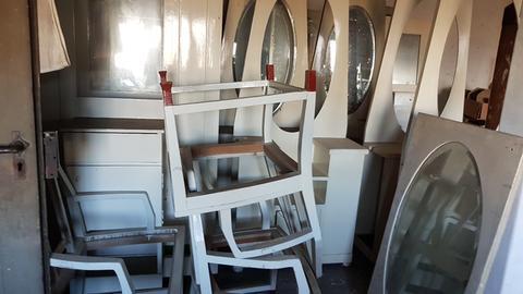 Weiße Jugendstilmöbel stapeln sich in einem Lagerraum