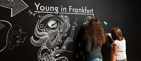 Besucher zeichnen mit Kreide auf einer großen Tafel im Historischen Museum Frankfurt.