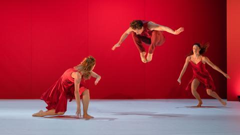 Drei rot gekleidete Schauspielerinnen auf der Bühne