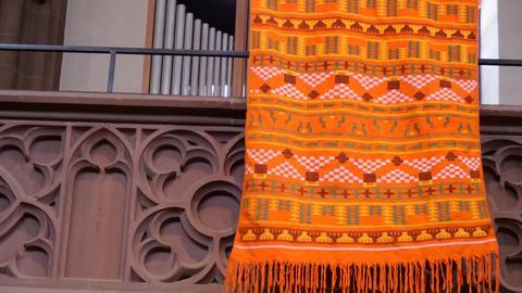 Ein gewebter Stoff (orange) hängt an der Dreikönigskirche in Frankfurt.
