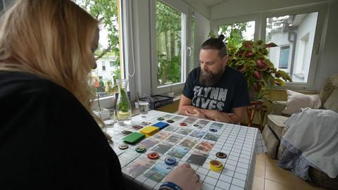 Das Bild zeigt eine blonde Frau und einen Mann mit Zopf. Sie sitzen an einem Holztisch an einem Fenster. Auf dem Tisch sind Spielkarten und -chips ausgebreitet.