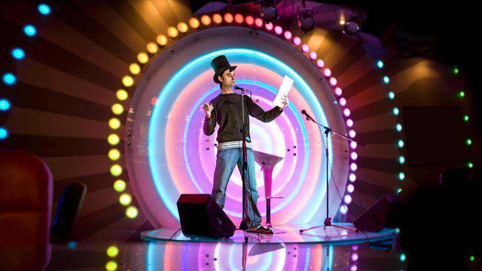 Ein Kleinkünstler auf der farbig beleuchteten Bühne.
