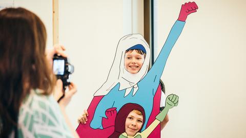 Kinder posieren in der Superheldenschablone im Kommunikationsmuseum in Frankfurt.