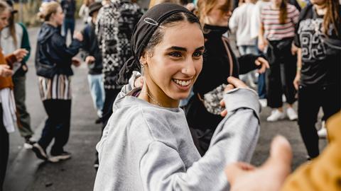 Junge Frau mit Kopftuch  tanzt im Freien