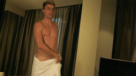 Ein nackter Mann, nur mit einem Handtuch um die Hüften, läuft durch ein mäßig beleuchtetes Zimmer.
