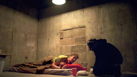Un uomo sdraiato su un letto che guarda ansiosamente la figura nel buio