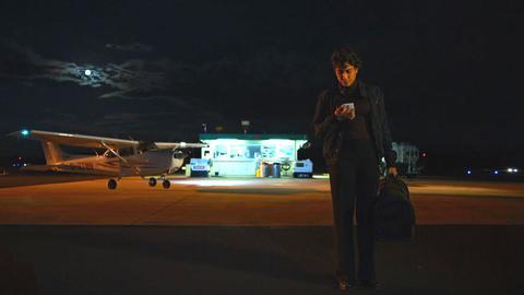 Scena notturna, uomo con un cellulare in un piccolo aeroporto