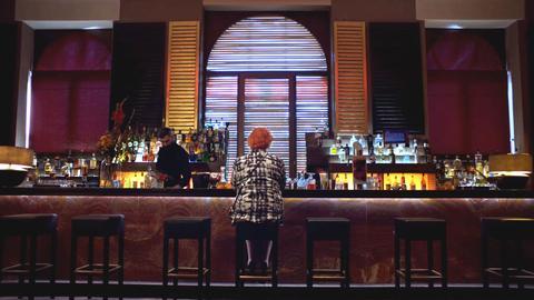 Scena notturna, donna sola al bar nel bar