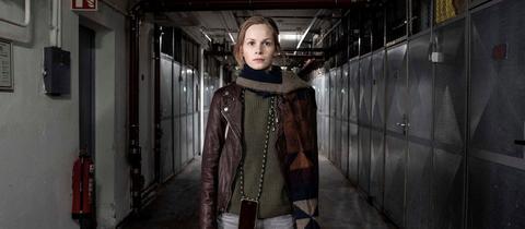 Emily steht in einem dunklen Gang der Kleinmarkthalle