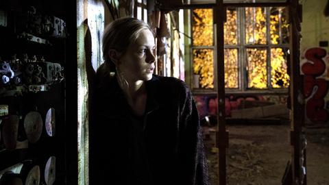 Emily steht vor einer Wand.