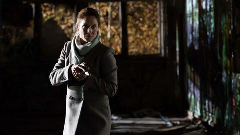 Gretchen Fisher mit gezogener Waffe.