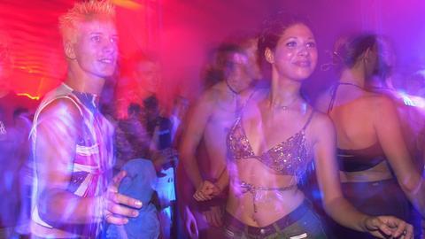 Zwei junge Leute tanzen in Disko-Licht