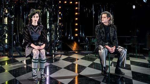 Proben zu Kasimir und Karoline in Kassel: Eine Schauspielerin und ein Schauspieler sitzen nebeneinander auf Stühlen und schauen ratlos aus.