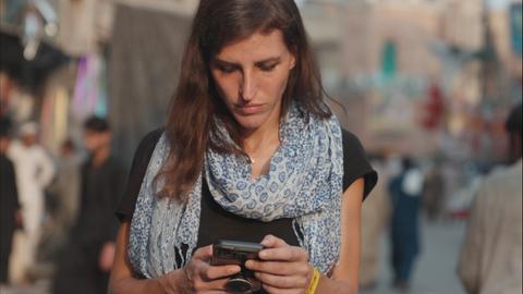 Eine Frau läuft mit dem Handy in der Hand durch eine von Menschen gesäumte Straße.